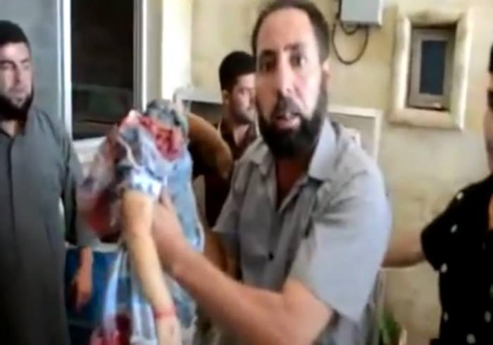 A distraught father in Syria holds the lifeless body of his decapitated daughter, executed by militants because she was of a Christian family. Allegedly, Christian children in Mosul are being systematically beheaded and their little heads placed on poles in a park as a warning to others who love their children.