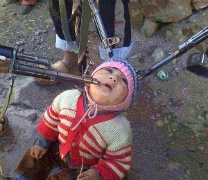 A child is photographed, waiting to be killed by militants. ISIS uses these images to terrorize others and to glorify their spree of terror.